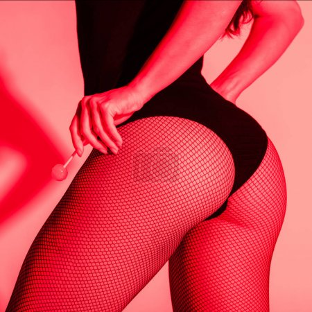 Photo pour Cropped view of sexy fesses of girl in fishnet tights holding lollipop in red light - image libre de droit
