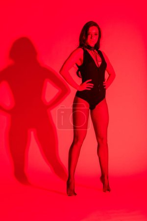 Photo for Beautiful sensual young woman posing in black leotard, isolated on red - Royalty Free Image