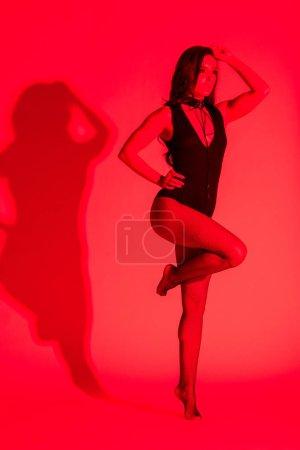 Photo pour Belle jeune femme passionnée posant en léotard noir, isolée sur rouge - image libre de droit