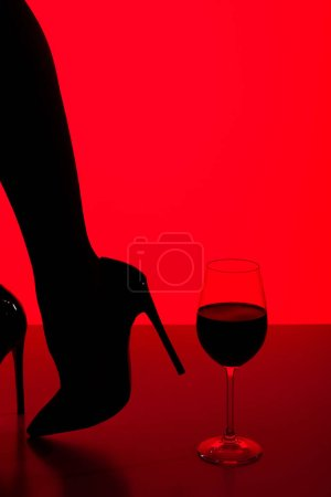 Photo for Partial view of silhouette of girl in heels with glass of wine isolated on red - Royalty Free Image