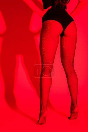 Photo for Cropped view of sexy buttocks and legs of girl on red - Royalty Free Image