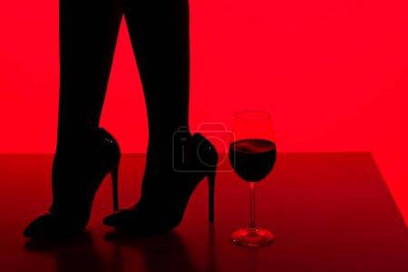 Photo pour Vue partielle de silhouette noire de fille en talons avec verre de vin isolé sur rouge - image libre de droit