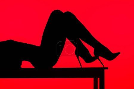 Photo for Black silhouette of sexy woman in heels lying on table, isolated on red - Royalty Free Image