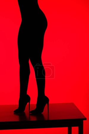 Photo for Black silhouette of sexy elegant woman in heels posing on table, isolated on red - Royalty Free Image