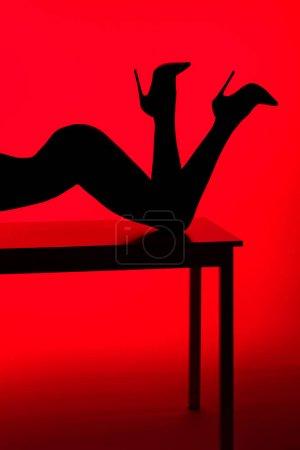 Photo pour Silhouette noire de fille passionnée en talons posant sur table isolée sur rouge - image libre de droit