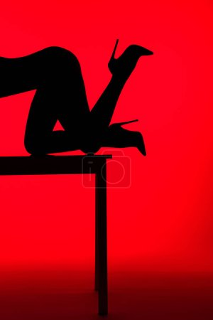 Photo for Black silhouette of passionate woman in heels posing on table isolated on red - Royalty Free Image