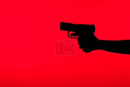 Photo for Cropped view of silhouette of criminal woman holding gun in hand isolated on red - Royalty Free Image