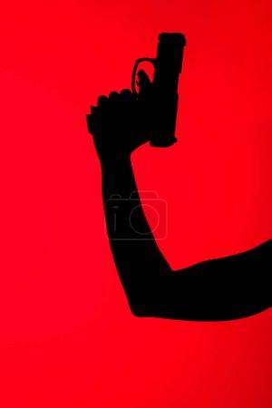 Photo pour Crochet vue de la silhouette d'une femme tenant son arme isolée sur du rouge - image libre de droit