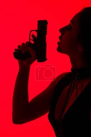Photo pour Silhouette de femme criminelle séduisante tenant arme isolée sur rouge - image libre de droit