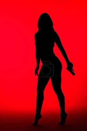 silueta de la mujer criminal en traje de cuerpo con arma aislada en rojo