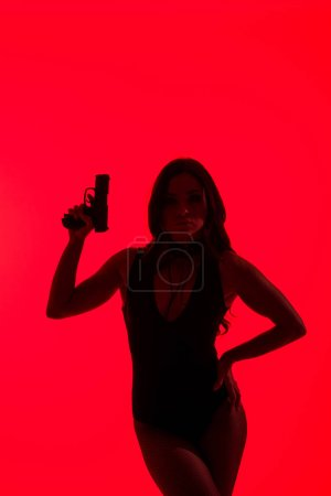 Photo for Silhouette of beautiful woman in bodysuit holding gun isolated on red - Royalty Free Image
