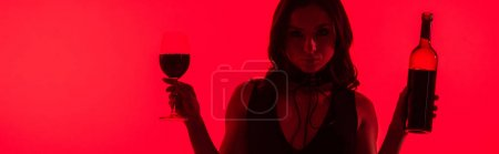 Photo for Panoramic shot of attractive sexy woman holding bottle and glass of wine isolated on red - Royalty Free Image