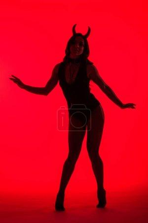 Photo pour Silhouette de séduisante femme sexy en costume de diable, isolée sur rouge - image libre de droit