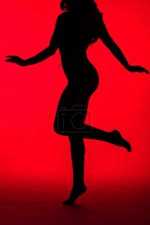 Photo pour Silhouette noire de femme sexy et élégante sur rouge - image libre de droit