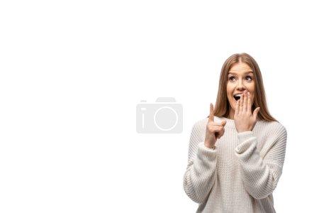 Photo pour Belle surprise femme en chandail blanc pointant vers le haut et couvrant la bouche, isolée sur blanc - image libre de droit