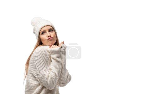 Foto de Atractiva mujer escéptica que pone en jersey y sombrero blanco, aislada sobre blanco. - Imagen libre de derechos