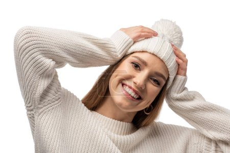 attractive smiling woman posing in white knitted sweater and hat, isolated on white