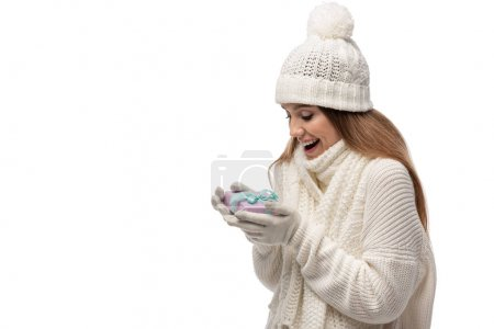 excited woman in scarf, gloves and hat looking at gift box, isolated on white