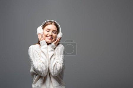 Photo pour Attrayante fille souriante posant dans un chandail blanc et des protège-oreilles, isolée sur gris - image libre de droit