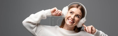 Photo for Panoramic shot of attractive happy girl posing in white sweater and earmuffs, isolated on grey - Royalty Free Image
