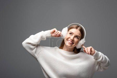 Photo pour Belle fille heureuse posant en pull blanc et chauffe-oreilles, isolé sur gris - image libre de droit