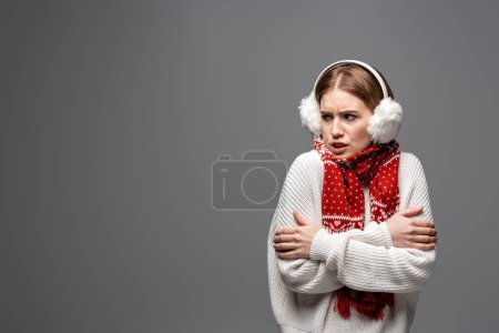 Photo pour Fille en colère froide en pull blanc, cache-oreilles et écharpe posant avec les bras croisés, isolé sur gris - image libre de droit