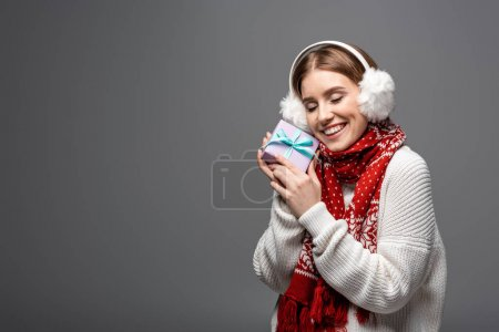 Photo pour Attractive happy woman in scarf and earmuffs holding christmas present, isolated on grey - image libre de droit