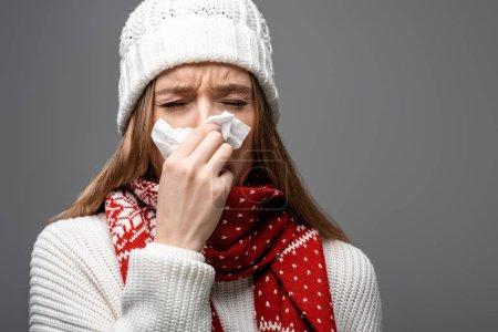 Photo pour Femme malade en bonnet tricoté au nez qui coule et tenant une serviette en papier, isolée sur gris - image libre de droit