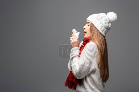 Photo pour Attractive ill girl in knitted hat sneezing with paper napkin, isolated on grey - image libre de droit