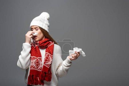 Photo pour Femme malade en bonnet tricoté et écharpe ayant le nez qui coule avec des serviettes en papier, isolé sur gris - image libre de droit