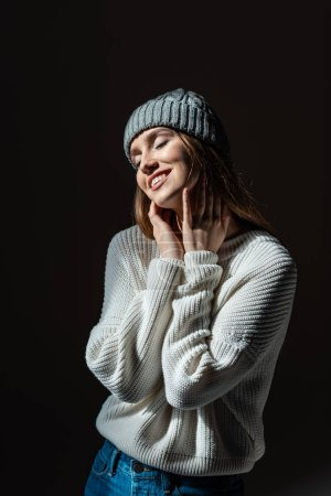 Photo for Beautiful dreamy tender girl with closed eyes in sweater and hat isolated on black - Royalty Free Image