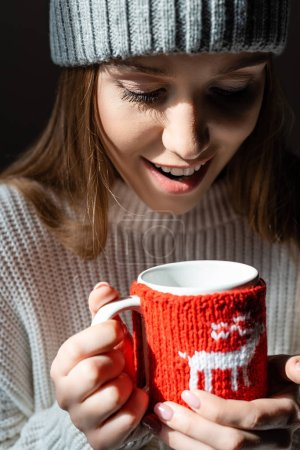 Photo pour Attractive positive woman holding christmas cup of coffee - image libre de droit