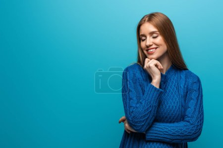 Photo for Attractive dreamy woman with closed eyes in blue knitted sweater, isolated on blue - Royalty Free Image