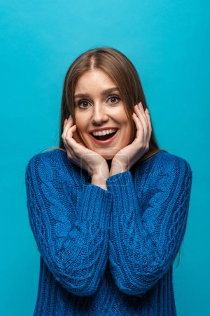 Photo for Attractive excited woman in blue knitted sweater, isolated on blue - Royalty Free Image