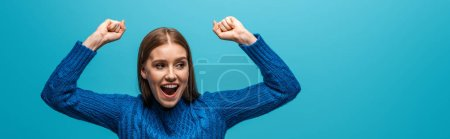 panoramic shot of attractive cheerful woman in blue knitted sweater celebrating triumph, isolated on blue