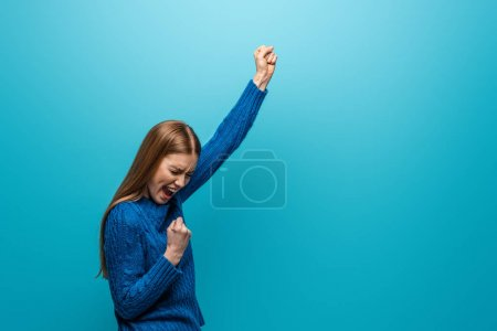 Photo for Beautiful cheerful woman in blue knitted sweater celebrating triumph, isolated on blue - Royalty Free Image