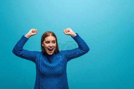 attraktive, glückliche Frau in blauem Strickpullover, die Erfolge feiert, isoliert auf blau