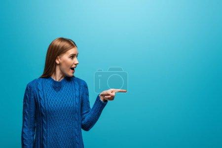 Foto de Hermosa mujer emocionada en sudor knitted azul señalando algo, aislado en azul. - Imagen libre de derechos