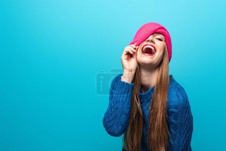 Foto de Atractivas mujeres graciosas reír en jersey y sombrero rosado, aisladas en azul. - Imagen libre de derechos