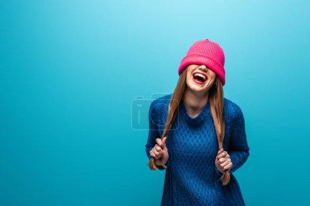 Foto de Jovencita mujer reír en un jersey teñido con sombrero rosa sobre los ojos, aislada sobre azul. - Imagen libre de derechos