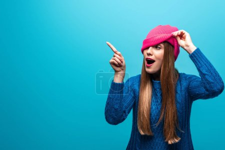 Photo for Beautiful happy woman pointing in knitted sweater and pink hat, isolated on blue - Royalty Free Image