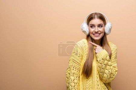 Photo pour Belle femme souriante pointant en pull jaune et cache-oreilles, isolée sur beige - image libre de droit