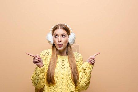 Photo pour Belle fille choquée en chandail jaune et oreillers pointant vers quelque chose, isolée sur beige - image libre de droit