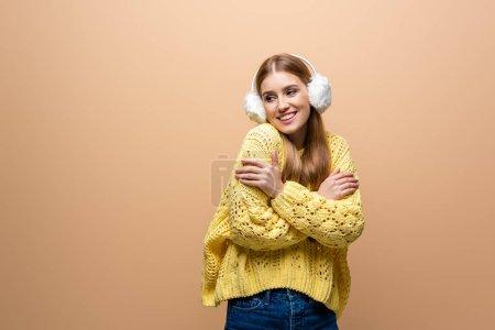 Foto de Mujeres sonrientes frías en sudor amarillo y calienta el oído, aisladas en beige. - Imagen libre de derechos