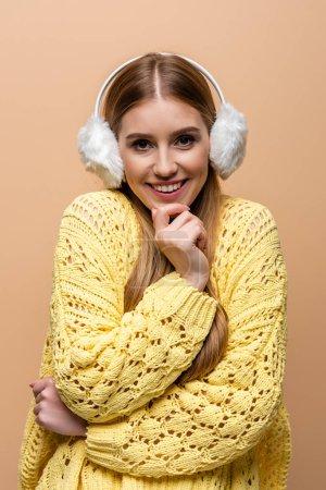 Photo pour Heureuse femme froide en pull jaune et cache-oreilles, isolé sur beige - image libre de droit
