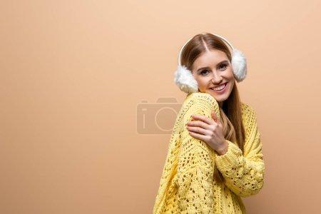 Photo pour Belle femme froide en chandail jaune et chauffe-oreilles, isolée sur beige - image libre de droit