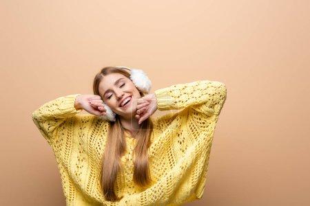 Photo pour Une femme rêveuse souriante aux yeux fermés en chandail jaune et aux oreilles, isolée sur beige - image libre de droit