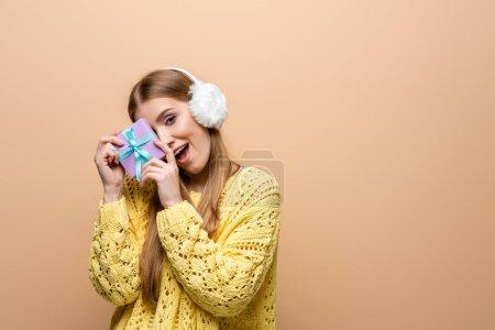 Photo pour Une femme excitée en chandail jaune et aux oreilles tenant un Noël présent, isolée sur beige - image libre de droit