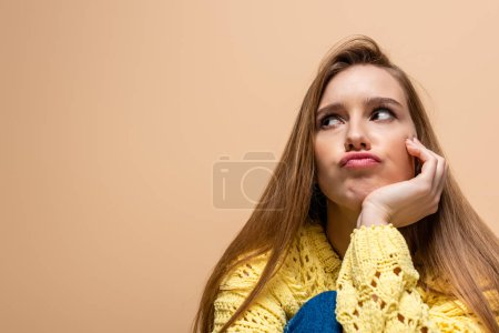 Photo for Beautiful offended woman in yellow sweater, isolated on beige - Royalty Free Image