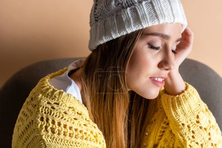 Photo for Attractive tender girl with closed eyes in yellow sweater and hat sitting in armchair on beige - Royalty Free Image